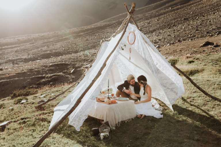 Couple sitting in a tent in Chile, on an adventure wedding. Glamping