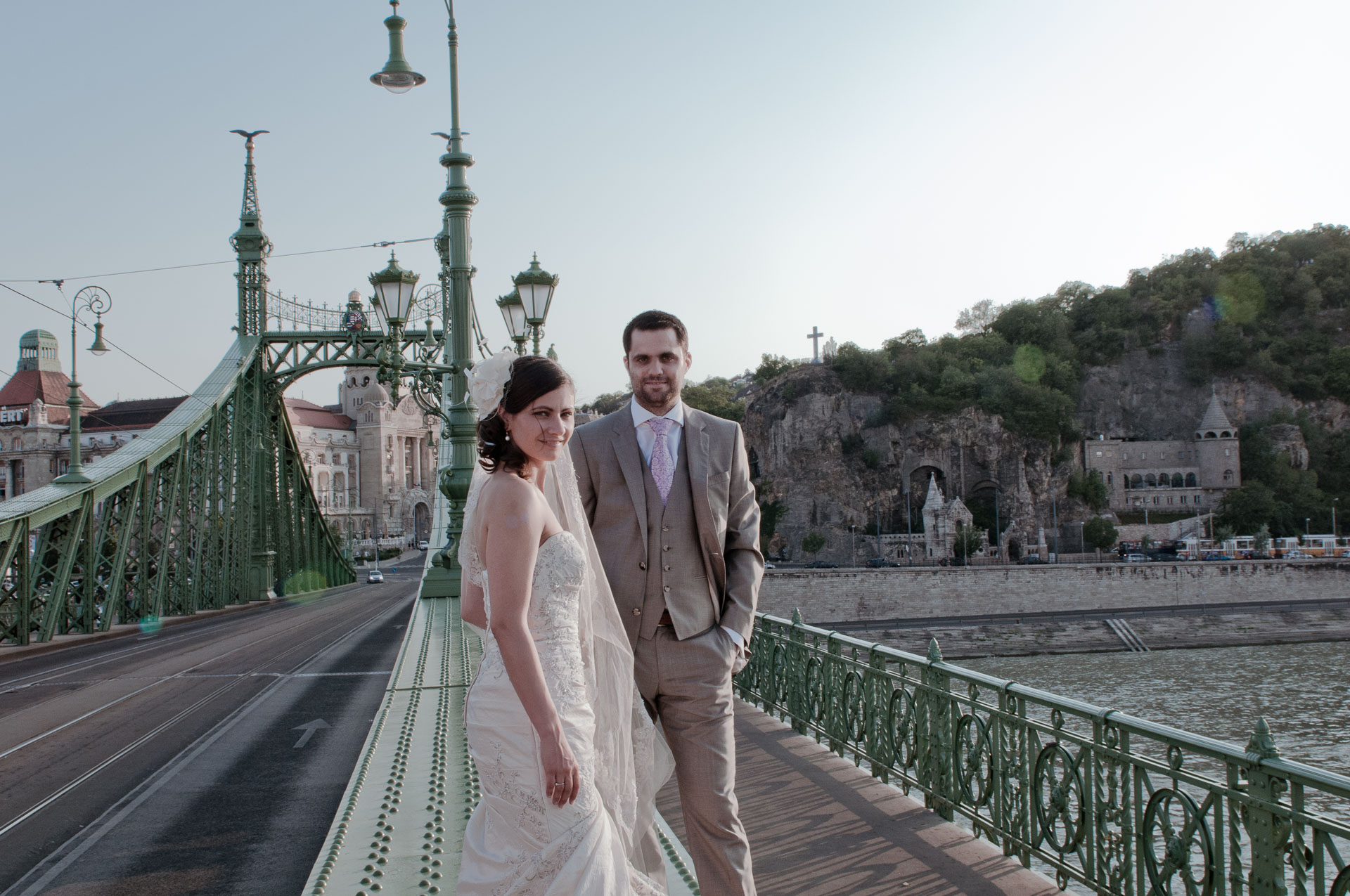Adventurous couple eloping into Budapest, posing on a bridge after spa visit