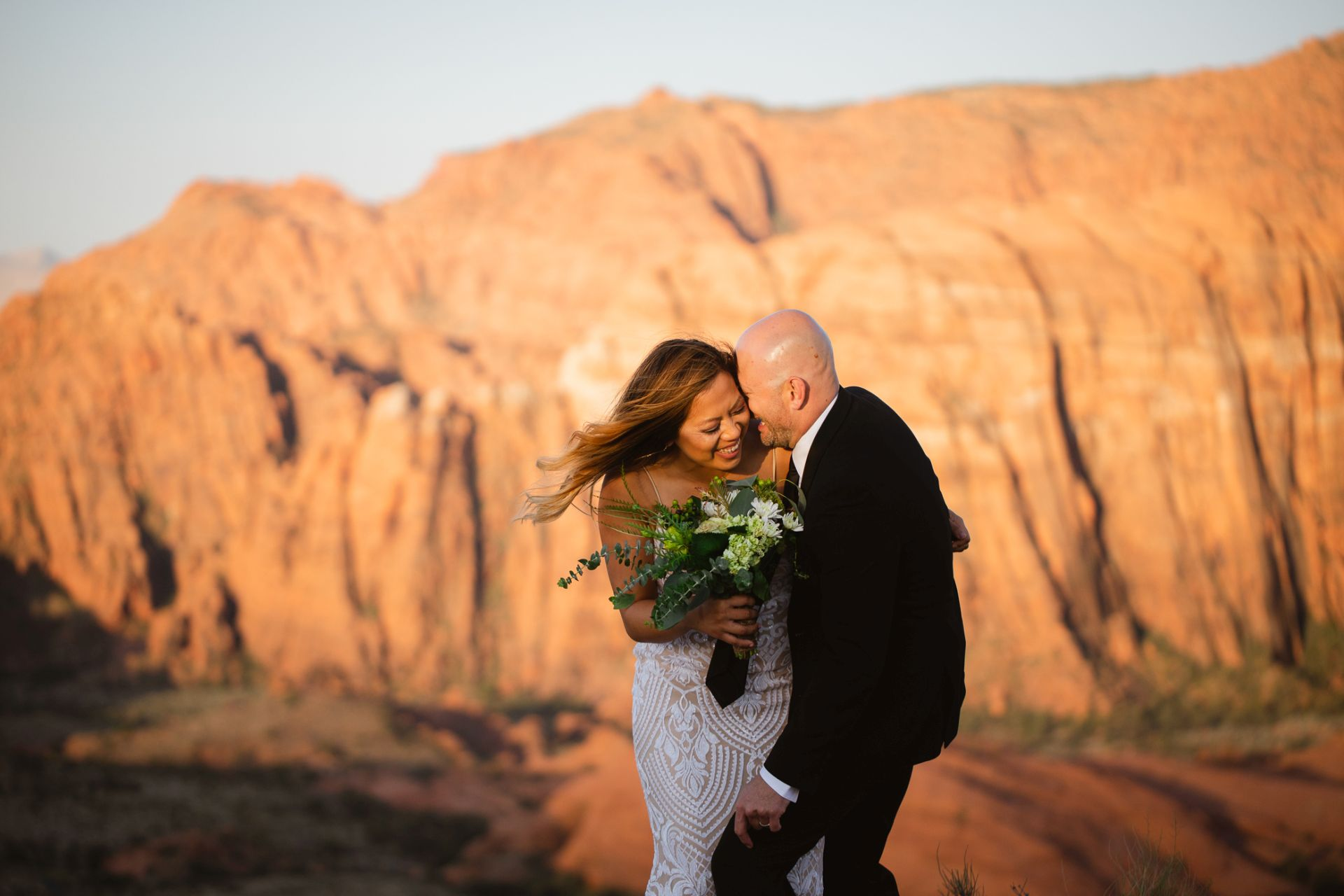 adventure wedding utah desert - photographer captures couple deeply in love before glowing mountain range