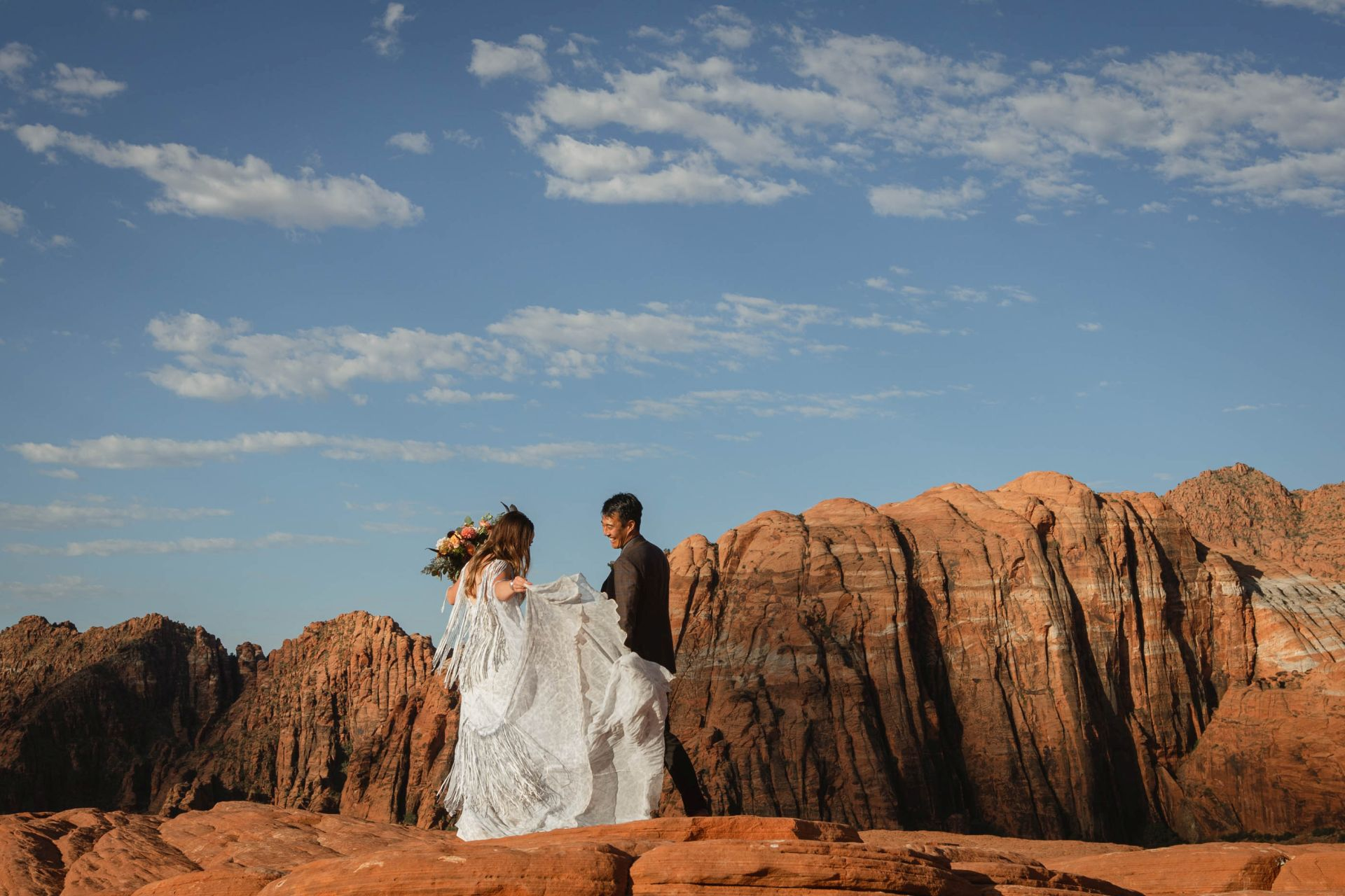Hike-out wedding in the desert of Utah - couple adventuring in front of spectacular striped mountain range